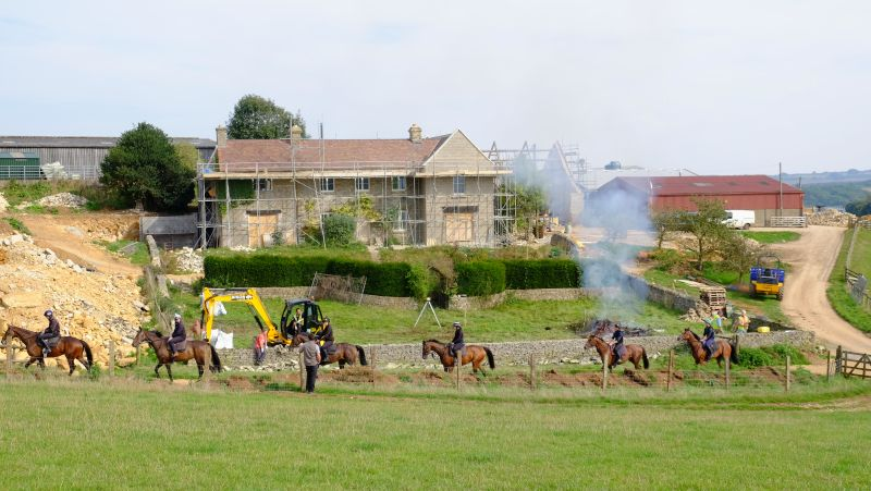 Horses passing the changing Thorndale farmhouse
